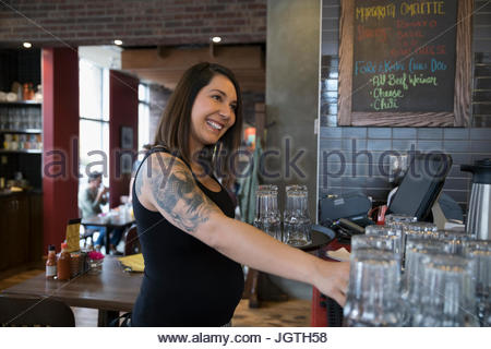 Smiling pregnant tattooed waitress using computer, inputting order in restaurant - Stock Photo