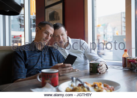 Male gay couple using cell phone in diner booth - Stock Photo