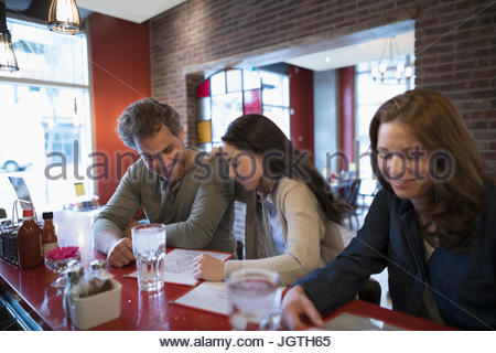 Father and teenage daughter looking at menu, dining at at diner counter - Stock Photo