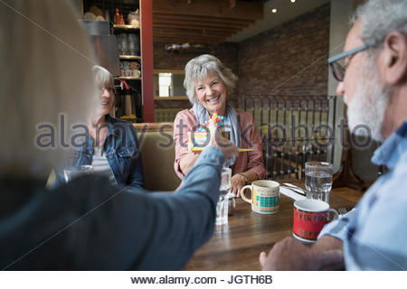 Smiling senior woman receiving birthday gift from friend in diner booth - Stock Photo