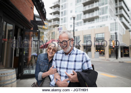 Smiling, affectionate senior couple walking on urban sidewalk - Stock Photo