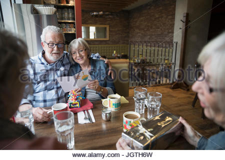 Senior friends celebrating birthday, reading greeting card in diner booth - Stock Photo
