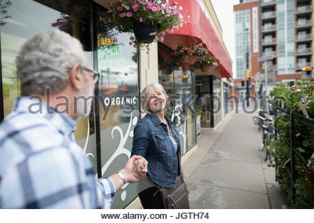 Affectionate senior couple holding hands, walking along storefront on urban sidewalk - Stock Photo