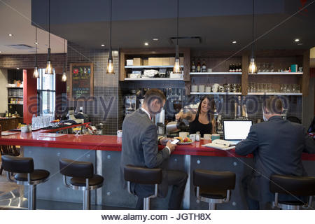 Tattooed waitress pouring coffee for businessmen working at laptop at cafe counter - Stock Photo