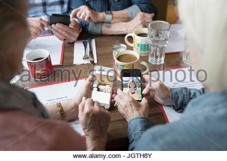 Senior women friends sharing digital photographs of grandchildren on camera phones in diner - Stock Photo