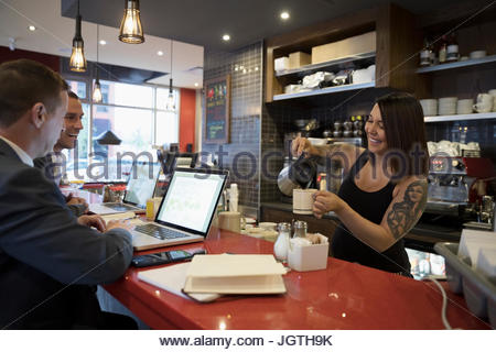 Tattooed waitress pouring coffee for businessmen working at laptops at cafe counter - Stock Photo
