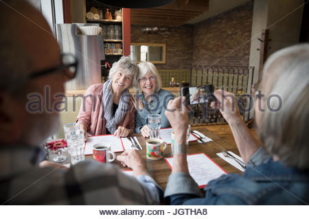 Senior woman photographing friends with camera phone in diner booth - Stock Photo