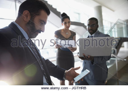 Businessman checking cell phone in office lobby - Stock Photo