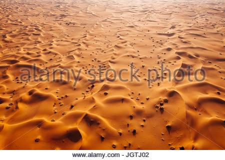 Aerial landscape photo of sand dunes of the Arabian desert during sunrise. - Stock Photo