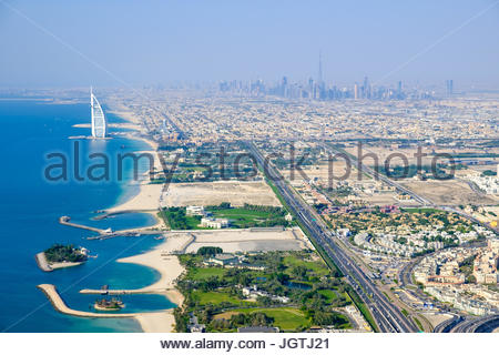 Aerial photo of Jumeirah beach, with the Burj Al Arab and downtown Dubai in the background - Stock Photo