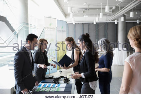 Business people arriving at conference check-in table - Stock Photo