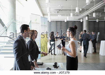 Businesswoman arriving at conference check-in table - Stock Photo