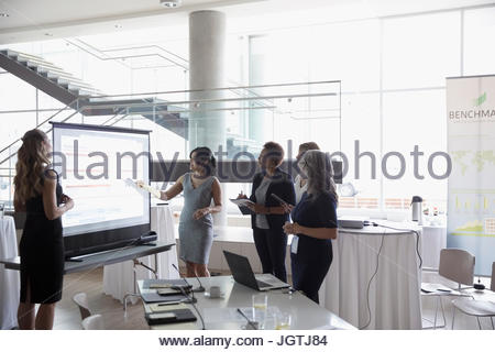 Businesswomen talking, planning at projection screen in conference meeting - Stock Photo