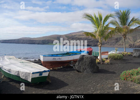 Fishing boats at the beach of the fishing village Playa Quemada, Lanzarote island, Canary islands, Spain, Europe - Stock Photo