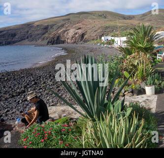 Girl sitting at volcanic pebble beach at the fishing village Playa Quemada, Lanzarote island, Canary islands, Spain, - Stock Photo