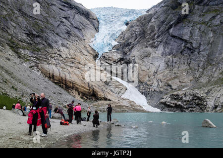 Tourists visiting Briksdalsbreen or Briksdal glacier arm of Jostedalsbreen above Briksdalsbrevatnet lake in Jostedalsbreen - Stock Photo