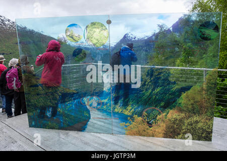 Tourists looking at view by Eagles Road viewpoint sign overlooking Geirangerfjorden. Geiranger, Sunnmøre region, - Stock Photo