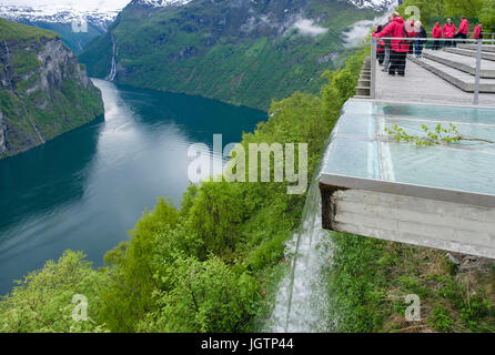 Artificial waterfall with tourists looking at view from high Eagles Road viewpoint platform overlooking Geirangerfjorden - Stock Photo