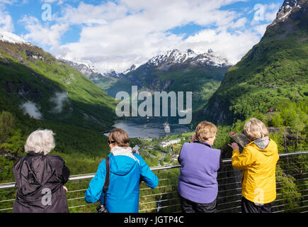 Four female tourists looking at scenic view from a viewpoint overlooking Geirangerfjorden fjord and village. Geiranger, - Stock Photo