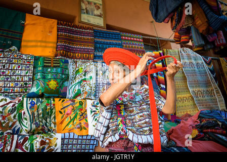 An older Indegenous Mayan woman wearing traditional dress, including a tocoyal or head wrap typical hat of Santiago - Stock Photo