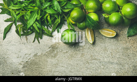 Flatlay of freshly picked organic limes and mint for making cocktail or lemonade over grey concrete stone background, - Stock Photo