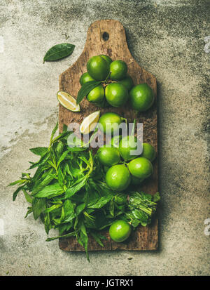 Flatlay of freshly picked organic limes and mint leaves for making cocktail or lemonade on wooden rustic board over - Stock Photo
