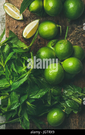 Flatlay of freshly picked organic limes and mint leaves for making cocktail or lemonade on wooden rustic board background, - Stock Photo