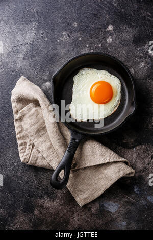 Fried egg on iron pan on dark background copy space - Stock Photo