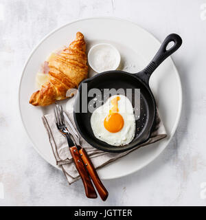 Breakfast with Fried egg on iron pan and croissant sandwich with cheese and ham on white plate on white background - Stock Photo