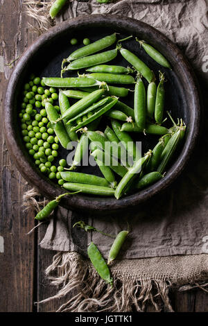 Young organic green pea pods and peas in terracotta tray over old dark wooden planks with sackcloth textile background. - Stock Photo