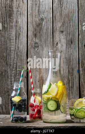 Citrus cucumber berries blueberry and rasberry sassy sassi water for detox in glass bottles with cocktail tubes - Stock Photo