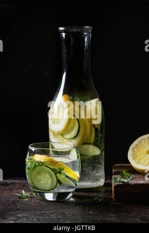Citrus cucumber sassy sassi water for detox in glass bottle on dark black background. Clean eating, healthy lifestyle - Stock Photo