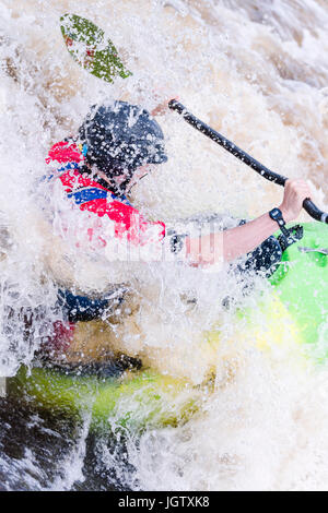 Male Kayak paddler in white water  performing a pirouette in a stopper wave on the Tees Barrage Whitewater Course - Stock Photo