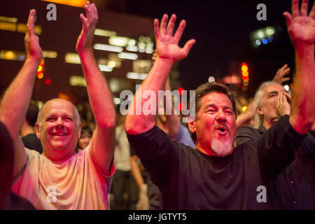 Montreal, 4 July 2017: Men cheering and smiling at the end of a concert at Montreal Jazz Festival - Stock Photo