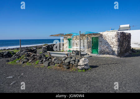 Small fishing house at the volcanic pebble beach, fishing village El Golfo, Lanzarote island, Canary islands, Spain, - Stock Photo