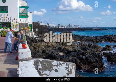 Elderlies at the coast, Punta Mujeres, fishing village north of Lanzarote, Canary islands, Europe - Stock Photo