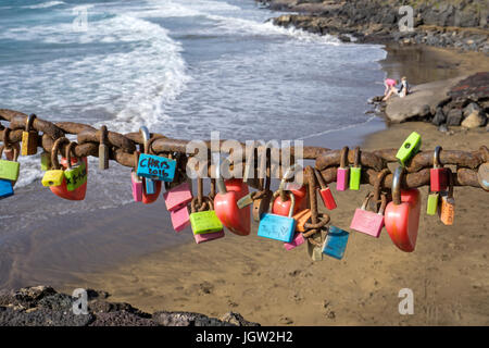 Love lockers hanging on chain at Playa Grande, large beach at Puerto del Carmen, Lanzarote island, Canary islands, - Stock Photo
