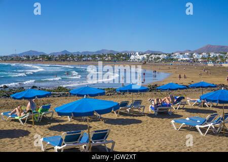 Blaue Sonnenliegen und Sonnenschirme am Playa Matagorda, grosser Badestrand in Puerto del Carmen, Lanzarote, Kanarische - Stock Photo