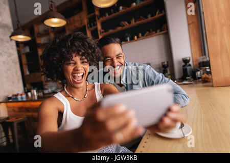 Happy young couple sitting together at cafe and taking selfie using mobile phone. African woman with her boyfriend taking self portrait with smart pho Stock Photo