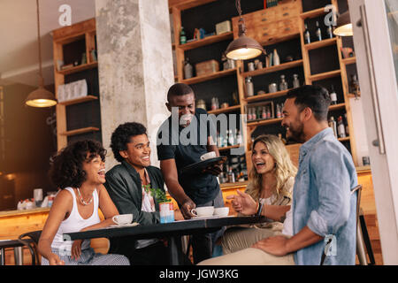 Group of friends sitting around table and waiter serving coffee at cafe. Young people meeting at coffee shop. - Stock Photo