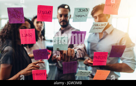 Business investors discussing work looking at the information on sticky notes stuck in office. Colleagues standing - Stock Photo