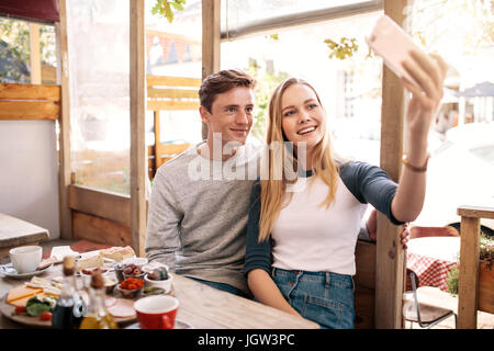 Couple taking photos of themselves with mobile phone in cafe. Stylish young couple catching memories by smart phone. - Stock Photo