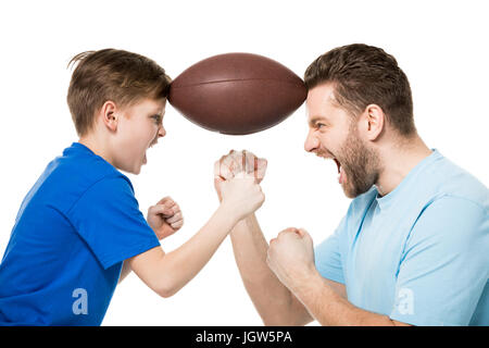 Side view of father with son screaming and holding rugby ball between faces isolated on white - Stock Photo