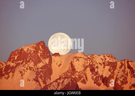 a full moon setting over Mount Humphreys mountain as the first light hits the summit - Stock Photo