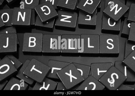 Black letter tiles spelling the word 'bills' on a reflective background - Stock Photo