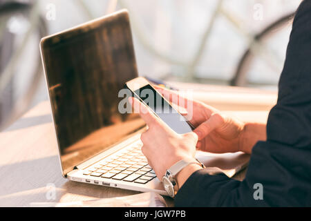 Close-up partial view of businesswoman using laptop and smartphone with blank screens - Stock Photo