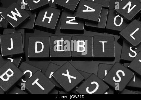 Black letter tiles spelling the word 'debt' on a reflective background - Stock Photo
