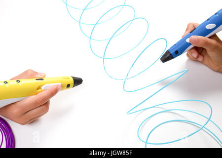 Kids hands holding 3d printing pens with filaments on white background. Top view - Stock Photo