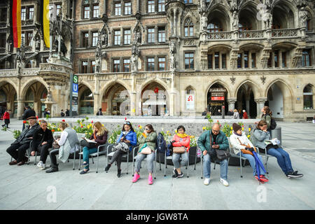 MUNICH, GERMANY - MAY 9, 2017 : People resting on chairs in front of New Town Hall at Marienplatz in Munich, Germany. - Stock Photo