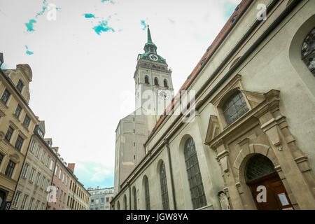 MUNICH, GERMANY - MAY 9, 2017 : A low angle view of the Saint Peters church clock tower among the city buildings - Stock Photo
